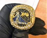This undated photo provided by U.S. Customs and Border Protection shows a fake Golden State Warriors championship ring, one in a collection of counterfeit NBA championship rings that have been seized by federal authorities at Los Angeles International Airport. CBP said Wednesday, Sept. 11, 2019, that the rings were in a wooden box shipped from China with a final destination in Arizona. Investigators suspect the intent was to sell the phony rings as a collection. (U.S. Customs and Border Protection via AP)