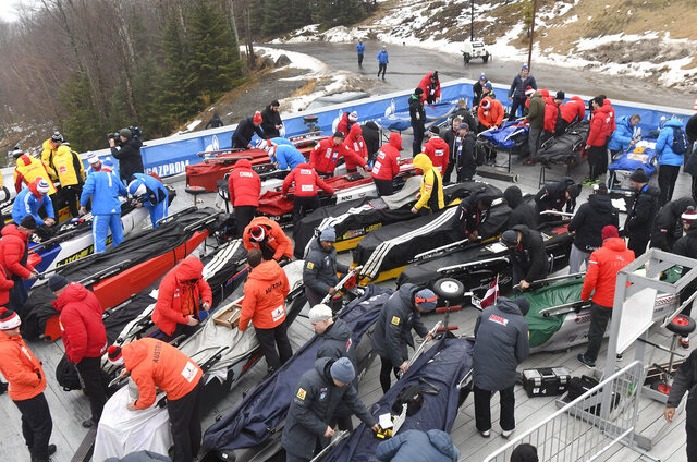 Bobsled team members ready their sleds for competition before the first run of the four-man bobsled World Cup race, in Lake Placid, N.Y., on Saturday, Dec. 14, 2019. (AP Photo/Hans Pennink)