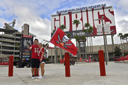 Season ticket holders, Jeremy and Daytona Stoner, of Tampa, take a photo of themselves outside an empty Raymond James Stadium before an NFL football game between the Tampa Bay Buccaneers and the Carolina Panthers Sunday, Sept. 20, 2020, in Tampa, Fla. Fans are not allowed in the stadium in an attempt to stop the spread of the coronavirus. (AP Photo/Jason Behnken)