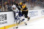 Boston Bruins' Torey Krug, right, checks Tampa Bay Lightning's Barclay Goodrow into the boards during the third period of an NHL hockey game Saturday, March 7, 2020, in Boston. (AP Photo/Winslow Townson)