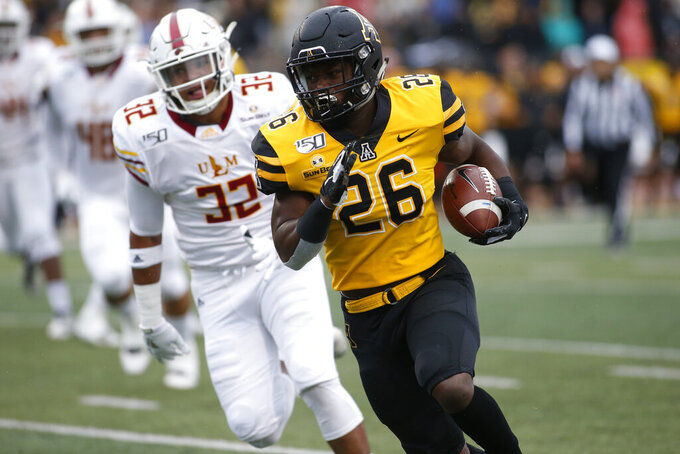 Appalachian State  running back Marcus Williams Jr. (26) evades Louisiana Monroe linebacker Chase Day (32) as he runs for a first down during the first half of an NCAA college football game Saturday, Oct. 19, 2019, in Boone, NC. (AP Photo/Brian Blanco)