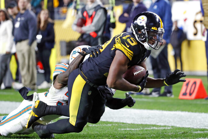 Pittsburgh Steelers wide receiver JuJu Smith-Schuster (19) falls into the end zone for a touchdown after taking a pass from quarterback Mason Rudolph with Miami Dolphins defensive back Chris Lammons (30) defending during the second half of an NFL football game in Pittsburgh, Monday, Oct. 28, 2019. (AP Photo/Don Wright)