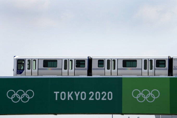 A train passes in the distance beyond the finish line of the BMX racing track as preparations continue for the 2020 Summer Olympics, Tuesday, July 20, 2021, at the Ariake Urban Sports Park in Tokyo. (AP Photo/Charlie Riedel)