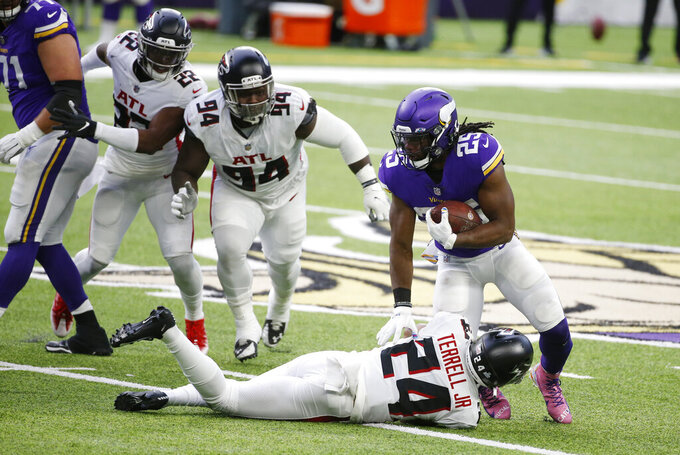 Minnesota Vikings running back Alexander Mattison (25) runs from Atlanta Falcons defenders A.J. Terrell (24), Deadrin Senat (94) and Keanu Neal (22) during the first half of an NFL football game, Sunday, Oct. 18, 2020, in Minneapolis. (AP Photo/Bruce Kluckhohn)