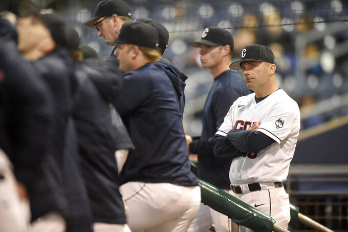 UConn baseball head coach Jim Penders, right, looks on with his players during an NCAA college baseball game against Tulane in Hartford, Conn., in this April 27, 2018, photo. Penders, the nephew of former college hoops coach Tom Penders, credits Connecticut's basketball programs and their combined 15 national titles, with creating an athletics culture that has helped him recruit top players to Storrs and convince officials to build his team's just opened state-of-the art Elliot Ballpark, which comes complete with an artificial turf field and heated benches. (John Woike/Hartford Courant via AP)