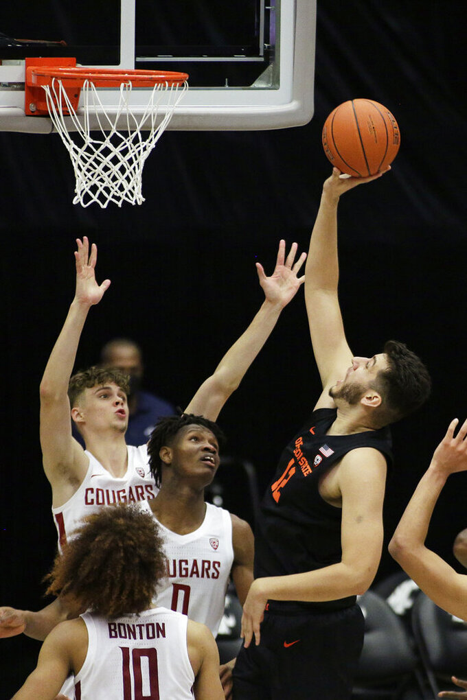 Oregon State center Roman Silva, right, shoots over Washington State forward Aljaz Kunc, left rear, and center Efe Abogidi during the second half of an NCAA college basketball game in Pullman, Wash., Wednesday, Dec. 2, 2020. Washington State won 59-55. (AP Photo/Young Kwak)