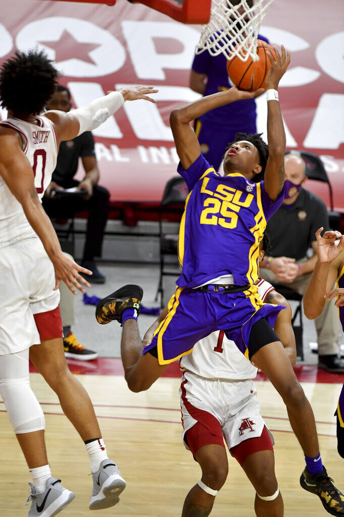 LSU guard Eric Gaines (25) drives past Arkansas defenders during the second half of an NCAA college basketball game in Fayetteville, Ark. Saturday, Feb. 27, 2021. (AP Photo/Michael Woods)