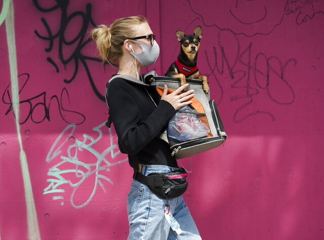 Tara Donsky walks with her dog along Queen Street West during the COVID-19 pandemic in Toronto on Monday, June 1, 2020.  (Nathan Denette/The Canadian Press via AP)