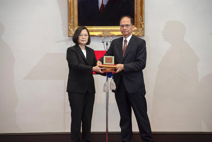 In this photo released by the Taiwan Presidential Office, Taiwanese President Tsai Ing-wen, left, holds up a seal with Parliament top speaker You Shi-kun during an inauguration ceremony at the Presidential office in Taipei, Taiwan on Wednesday, May 20, 2020. Tsai has been inaugurated for a second term amid increasing pressure from China on the self-governing island democracy it claims as its own territory. (Taiwan Presidential Office via AP)