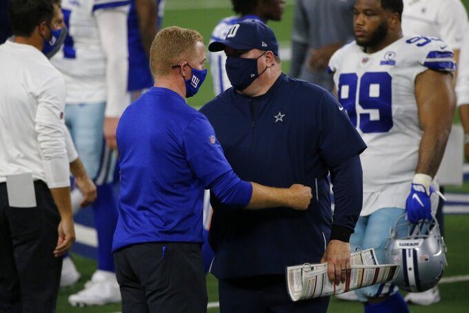 New York Giants offensive coordinator Jason Garrett, left, and Dallas Cowboys head coach Mike McCarthy, right, greet each other after their NFL football game in Arlington, Texas, Sunday, Oct. 11, 2020. (AP Photo/Michael Ainsworth)