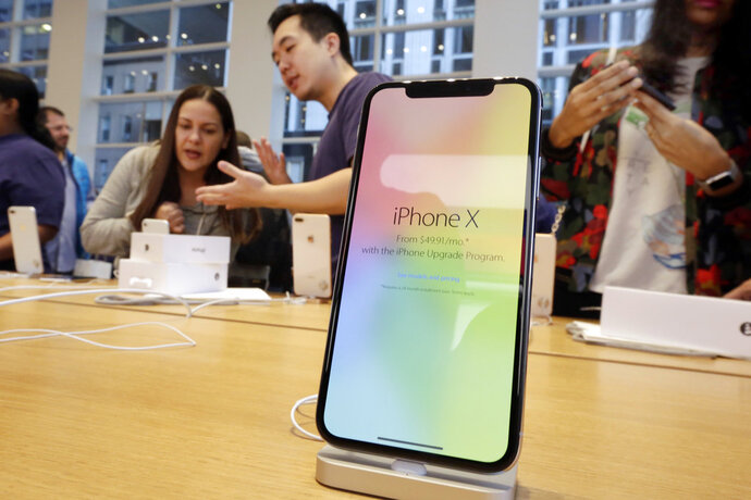 FILE - In this Nov. 3, 2017, file photo, customers buy the iPhone X at the Apple Store on New York's Fifth Avenue. Apple is expected to unveil its biggest and most expensive iPhone on Wednesday, Sept. 12, 2018, as part of a lineup of three new models aimed at widening the product's appeal amid slowing sales growth. (AP Photo/Richard Drew, File)