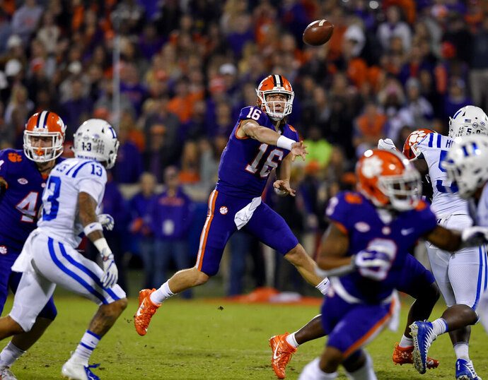 FILE - In this Nov. 17, 2018, file photo, Clemson quarterback Trevor Lawrence throws a pass under pressure during the first half of an NCAA college football game against Duke, in Clemson, S.C. For the first time, the defending national champion Tigers are No. 1 in The Associated Press preseason Top 25 presented by Regions Bank, Monday, Aug. 19, 2019. Clemson won its second national title in three seasons behind freshman quarterback Trevor Lawrence to claim equal standing with Alabama at the top of the sport. (AP Photo/Richard Shiro, File)