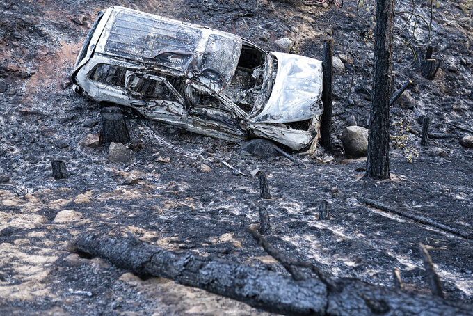 A burned car damaged by the Bootleg Fire is seen here along a mountain road on Wednesday, July 21, 2021 near Bly, Ore. (AP Photo/Nathan Howard)