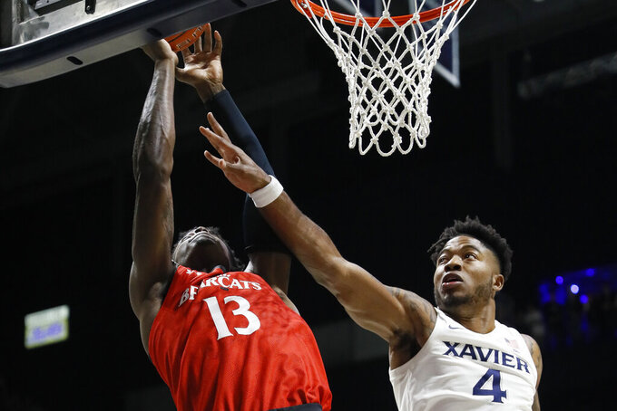 Cincinnati's Jeremiah Davenport (1) shoots against Xavier's Tyrique Jones (4) during the first half of an NCAA college basketball game, Saturday, Dec. 7, 2019, in Cincinnati. (AP Photo/John Minchillo)