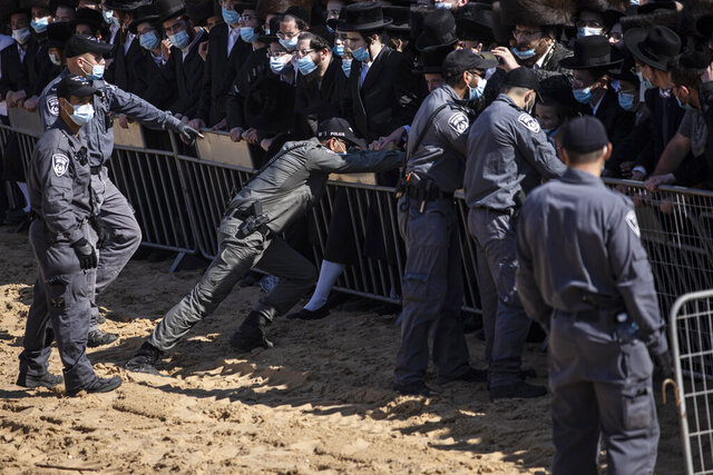 Israeli police try to control a crowd of mourners during the funeral of Rabbi Mordechai Leifer, the latest in a string of clashes between security forces and ultra-Orthodox Jews violating a national coronavirus lockdown order, in the port city of Ashdod, Israel, Monday, Oct. 5, 2020. The late rabbi, who had been the spiritual leader of a small ultra-Orthodox community founded a century ago in the U.S. city of Pittsburgh, died Sunday after a long bout with COVID-19. (AP Photo/Tsafrir Abayov)