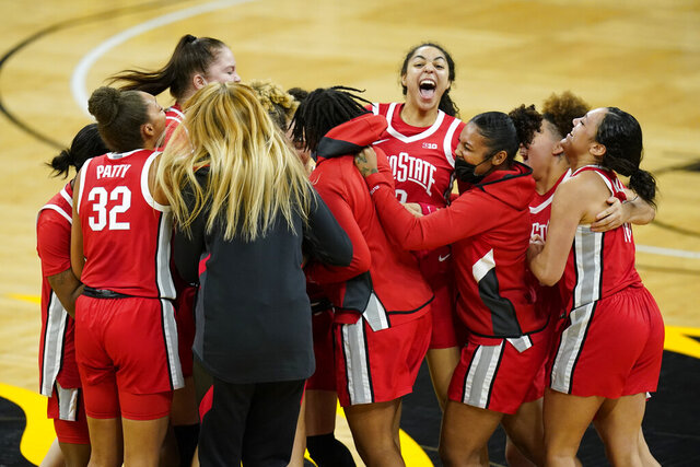 Ohio State players celebrate on the court after their 84-82 overtime victory over Iowa in an NCAA college basketball game, Wednesday, Jan. 13, 2021, in Iowa City, Iowa. (AP Photo/Charlie Neibergall)