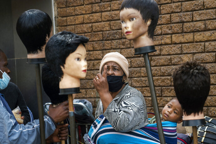 A woman carrying a child on her back looks at wigs on sale at the Baragwanath Taxi Rank in Soweto, South Africa, Wednesday, Sept. 16, 2020. South African president Cyril Ramaphosa is scheduled to address the nation later in the day, as case numbers and death from COVID-19 hit the lowest in months. (AP Photo/Jerome Delay)