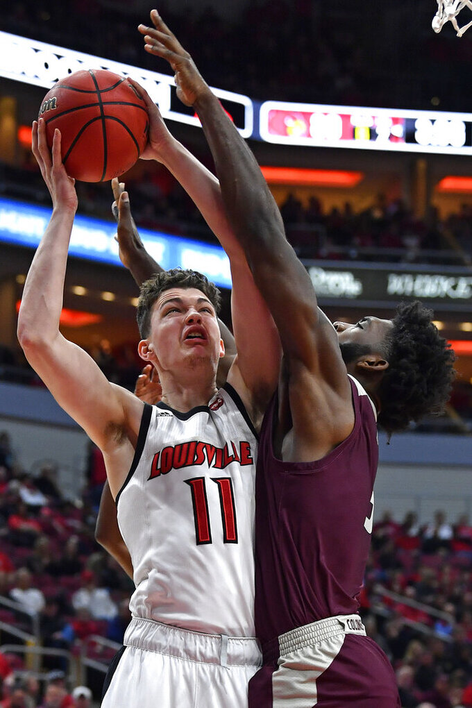 Louisville forward Quinn Slazinski (11) attempts a shot between the defensive pressure of Eastern Kentucky forward Darius Hicks, right, and guard Ty Taylor II, rear, during the second half of an NCAA college basketball game in Louisville, Ky., Saturday, Dec. 14, 2019. Louisville won 99-67. (AP Photo/Timothy D. Easley)