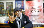 """In this Oct. 11, 2019, photo, Japanese director Nobuhiko Obayashi holds up his hand in the sign language of """"I love you"""" to stress that is an important message in his films, during an interview at his studio in Tokyo. Obayashi has been diagnosed with fatal lung cancer, but his confrontation with death began so long ago it has characterized his entire four decades of filmmaking. Obayashi has stayed true to himself during that whole time, producing more than 40 movies and thousands of TV shows, commercials and other video, devoted to sending the same message, over and over, to warn the world of the horrors of war. (AP Photo/Yuri Kageyama)"""