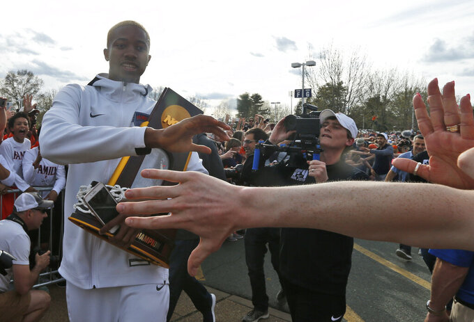 Mamadi Diakite hoods the NCAA championship trophy as Virginia team members are welcomed by fans as they return to Charlottesville, Va., Tuesday, April 9, 2019, the day after defeating Texas Tech in the title game of college basketball's Final Four. (AP Photo/Steve Helber)