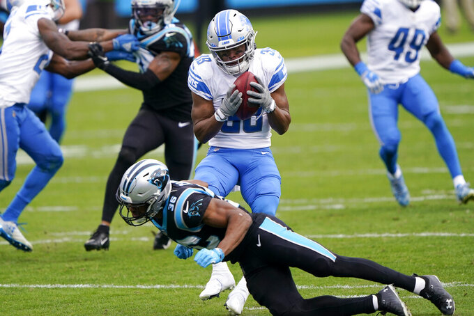 Detroit Lions wide receiver Jamal Agnew catches a pass over Carolina Panthers' Trenton Cannon during the first half of an NFL football game Sunday, Nov. 22, 2020, in Charlotte, N.C. (AP Photo/Brian Blanco)