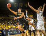 FILE - In this Dec. 1, 2018, file photo, Purdue guard Carsen Edwards, left, attempts a layup while defended by Michigan guard Zavier Simpson (3) and forward Ignas Brazdeikis (13) in the first half of an NCAA college basketball game, in Ann Arbor, Mich. Edwards was named to the All-Big Ten Conference team, Tuesday, March 12, 2019.  (AP Photo/Tony Ding, File)