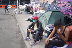 """Sotero Cirilo, center, sits on the sidewalk at the homeless encampment where he sleeps in the Queens borough of New York, Wednesday, April 14, 2021. The 55-year-old immigrant from Mexico used to make $800 per week at two Manhattan restaurants, which closed when the COVID-19 pandemic started. A few months later, he couldn't afford the rent of his Bronx room, and afterward, of another room in Queens he moved into. """"I never thought I would end up like this, like I am today,"""" he said, his eyes filling up with tears. (AP Photo/Seth Wenig)"""