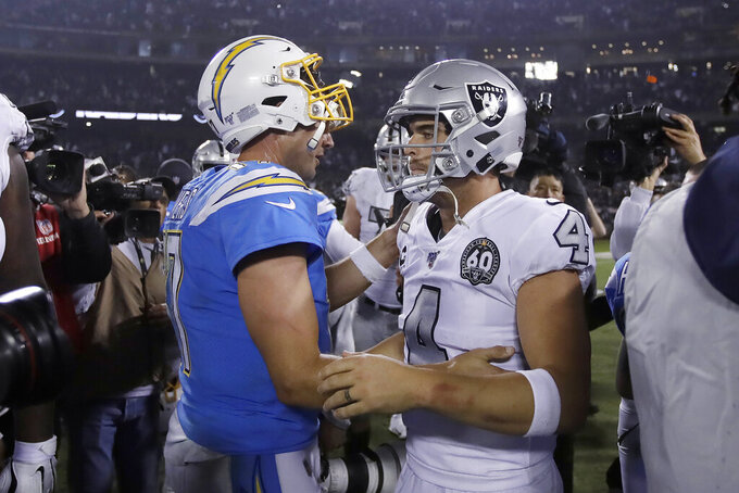 Los Angeles Chargers quarterback Philip Rivers, left, greets Oakland Raiders quarterback Derek Carr after the Raiders defeated the Chargers 26-24 in an NFL football game in Oakland, Calif., Thursday, Nov. 7, 2019. (AP Photo/Ben Margot)