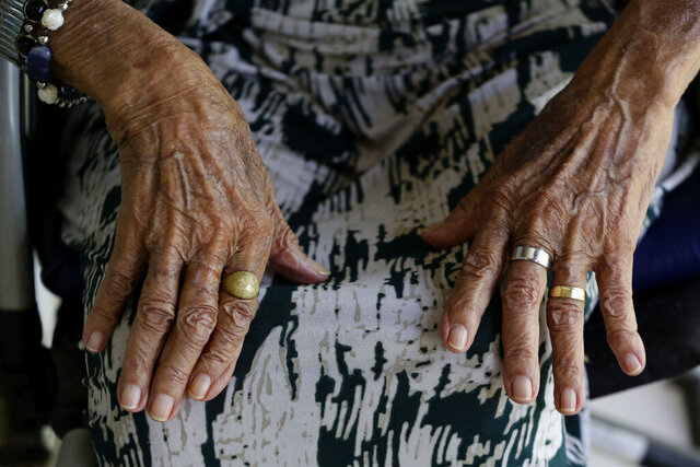 Francisca Alves Xavier, 102, who has already been infected with COVID-19, rests her hands on her legs before getting a shot of China's Sinovac CoronaVac vaccine as part of a priority COVID-19 vaccination program for the elderly at the Bezerra de Menezes Asylum in Brasilia, Brazil, Friday, Jan. 22, 2021. Xavier said she feels free now because she will be able to hug her friends and see his family again. (AP Photo/Eraldo Peres)
