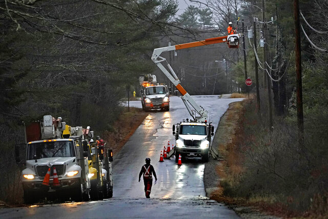 A crew from New Brunswick, Canada, works to restore power following a severe rain storm, Tuesday, Dec. 1, 2020, in Brunswick, Maine. The storm knocked out power to  more than 100,000 electricity customers in Maine. (AP Photo/Robert F. Bukaty)