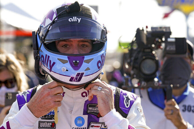 Jimmie Johnson prepares his helmet before getting in his car to start of the Rolex 24 hour auto race at Daytona International Speedway, Saturday, Jan. 30, 2021, in Daytona Beach, Fla. (AP Photo/John Raoux)