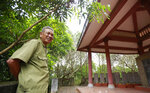 In this Feb. 16, 2019, photo, veteran Duong Van Dau smiles while standing at a memorial for North Korean fallen pilots in Bac Giang province, Vietnam. The fourteen headstones of the pilots who died while fighting American bombers alongside the Vietnamese army during the Vietnam war remain as a symbol of Vietnam-North Korea friendship. (AP Photo/Hau Dinh)
