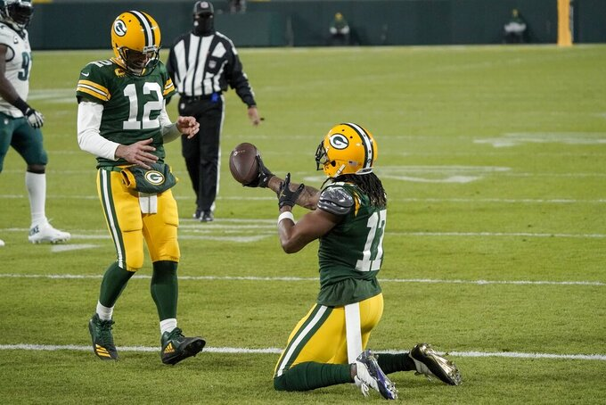 Green Bay Packers' Davante Adams hands the ball to quarterback Aaron Rodgers after catching a touchdown pass during the second half of an NFL football game against the Philadelphia Eagles Sunday, Dec. 6, 2020, in Green Bay, Wis. The pass was Rodgers' 400th career touchdown pass. (AP Photo/Morry Gash)