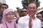 Politician Anwar Ibrahim, right, and his wife Wan Azizah Ismail waves as they heading to their party headquarters for a press conference after meeting the king in Kuala Lumpur, Malaysia, Wednesday, Feb. 26, 2020. Malaysia's king held unusual consultations with lawmakers for a second day Wednesday to resolve a political vacuum caused by the abrupt collapse of the ruling coalition and the resignation of Prime Minister Mahathir Mohamad. (AP Photo)