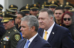 Colombia's President Ivan Duque, front, and US Secretary of State Mike Pompeo walk after attending a ceremony marking one year since a car bomb attack at the police academy in Bogota, Colombia, during the inauguration of a regional anti-terrorism summit, Monday, Jan. 20, 2020. The Colombian government blamed rebels of the National Liberation Army, ELN, for the bombing that killed at least 21 people on Jan. 17, 2019. (AP Photo/Ivan Valencia)