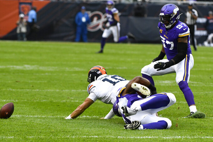 Chicago Bears quarterback Mitchell Trubisky (10) is injured as he fumbles and is pulled down by Minnesota Vikings defensive end Danielle Hunter and Vikings defensive end Everson Griffen (97) watches during the half of an NFL football game Sunday, Sept. 29, 2019, in Chicago. (AP Photo/Matt Marton)