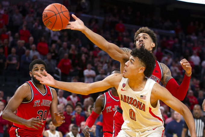 St. John's forward Damien Sears, top, knocks the ball away from Arizona guard Josh Green (0) during the second half of an NCAA college basketball game Saturday, Dec. 21, 2019, in San Francisco. St. John's won 70-67. (AP Photo/D. Ross Cameron)
