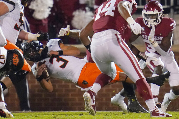 Oklahoma State quarterback Spencer Sanders (3) is brought down by Oklahoma defenders during the second half of an NCAA college football game in Norman, Okla., Saturday, Nov. 21, 2020. (AP Photo/Sue Ogrocki)