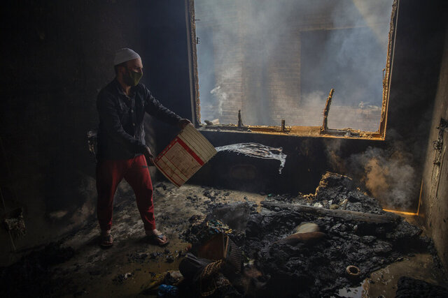 A Kashmiri man douses a fire in a house which was damaged in a gun-battle in Srinagar, Indian controlled Kashmir, Tuesday, May 19, 2020. Indian government forces killed two rebels in disputed Kashmir on Tuesday and shut down cellphone and mobile internet services during subsequent anti-India protests, officials and residents said. (AP Photo/ Dar Yasin)