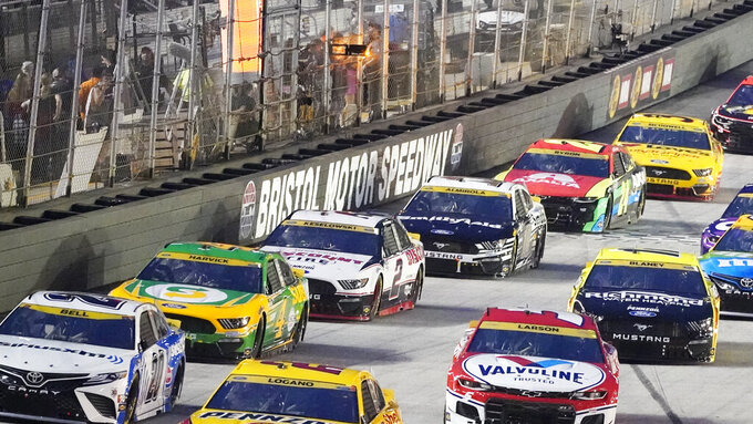 Cars come down a straightaway during a NASCAR Cup Series auto race at Bristol Motor Speedway Saturday, Sept. 18, 2021, in Bristol, Tenn. (AP Photo/Mark Humphrey)