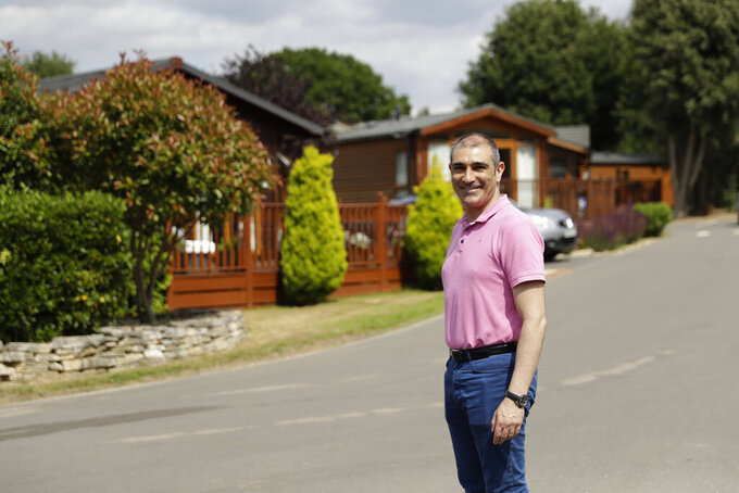 General manager Philip Pantelis poses for photographs at the Edgeley Holiday Park in Farley Green, near Guildford, south west of London, Wednesday, July 22, 2020. With all schools now closed, Friday would normally be the busiest departure day of the year for London's Gatwick Airport with families heading off to the sun-soaked beaches in southern Europe. Not this year as the coronavirus pandemic has meant many have opted against making their annual summer migration to countries like Spain and Greece. Gatwick would in any normal year be expecting to fly some 85,000 holidaymakers on Friday alone. It expects less than 10,000 passenger departures on Friday. (AP Photo/Matt Dunham)