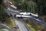 FILE - In this Dec. 18, 2017 file photo, cars from an Amtrak train that derailed lie spilled in DuPont, Wash. Federal investigators are hearing from witnesses as they look into last year's Amtrak train derailment south of Seattle, Wash., that killed three people and injured dozens. (Bettina Hansen/The Seattle Times via AP, File)