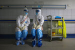 In this Sunday, Feb. 16, 2020, photo, medical workers wearing full protective suits chat to each other at a hospital in Wuhan in central China's Hubei province. Chinese authorities on Monday reported a slight upturn in new virus cases and hundred more deaths for a total of thousands since the outbreak began two months ago. (Chinatopix via AP)