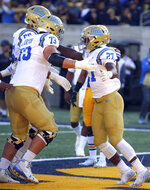 UCLA running back Joshua Kelley, right, celebrates with Jake Burton (73) after scoring a touchdown against California during the first half of an NCAA college football game Saturday, Oct. 13, 2018, in Berkeley, Calif. (AP Photo/Ben Margot)
