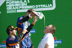 Zak Brown, right, drinks champagne from a shoe flanked by Mclaren drivers Daniel Ricciardo of Australia, left, and Britain's Lando Norris, following the Formula One Grand Prix, at the Monza racetrack, Italy, Sunday, Sept. 12, 2021. Zak Brown returned to his home state at the top of the motor sports world following the 1-2 finish by McLaren at the Italian Grand Prix. It was the defining moment of a career that began as the wannabe racer from California climbed the motorsports ladder to CEO of McLaren Racing. Just seven days later, Brown was at Laguna Seca to watch McLaren's IndyCar team battle for the championship. (AP Photo/Luca Bruno)