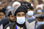 Delegates wearing a protective face masks to help curb the spread of the coronavirus attend an Afghan Loya Jirga meeting in Kabul, Afghanistan, Friday, Aug. 7, 2020. The traditional council opened Friday in the Afghan capital to decide the release of a final 400 Taliban - the last hurdle to the start of negotiations between Kabul's political leadership and the Taliban in keeping with a peace deal the United States signed with the insurgent movement in February. (AP Photo/Rahmat Gul)