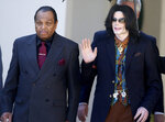 FILE - In this March 15, 2005 file photo, pop star Michael Jackson, right, leaves the Santa Barbara County Courthouse with his father, Joe Jackson, in Santa Maria, Calif. (AP Photo/Michael A. Mariant, File)