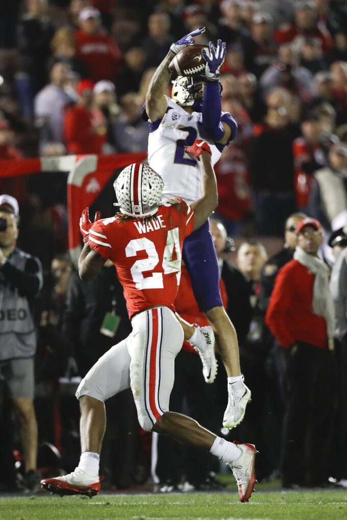 Washington wide receiver Aaron Fuller catches a pass over Ohio State cornerback Shaun Wade during the second half of the Rose Bowl NCAA college football game Tuesday, Jan. 1, 2019, in Pasadena, Calif. (AP Photo/Jae C. Hong)