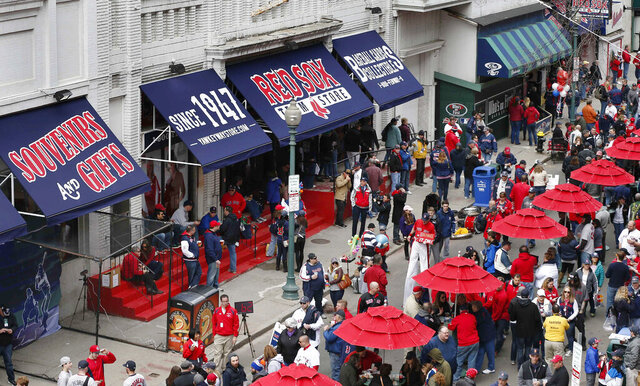FILE - In this April 4, 2014 file photo, fans enjoy pre-game festivities outside Fenway Park in Boston. Ballpark area businesses are struggling during the 2020 season while fans are not in attendance due to the COVID-19 pandemic. (AP Photo/Michael Dwyer, File)