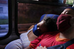 Ada Mendoza, 24, rests her head on the shoulder of her partner Leo Camejo, as they return home on a bus after a prenatal visit to a private clinic in Caracas, Venezuela, Monday, Sept. 7, 2020. Despite being afraid of becoming infected with the new coronavirus, the couple has no choice but to board two buses to get to the prenatal care appointments. (AP Photo/Matias Delacroix)